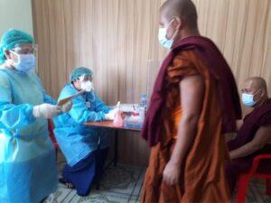 個人防護具をつけた医療者と患者である僧